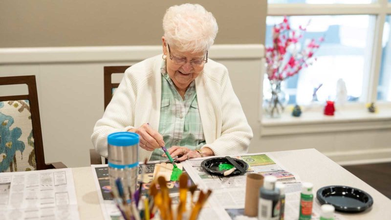 Senior woman seated at table painting